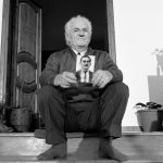 BESA: Sazan Hoxha with photograph of his father, Nuro Hoxha, Photographer: Norman H. Gershman